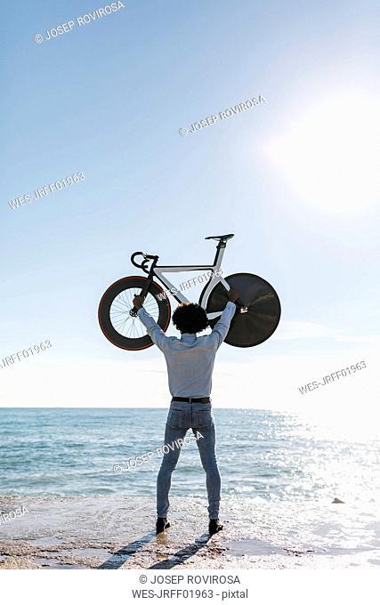 Man lifting his bike on the beach, watching the sea