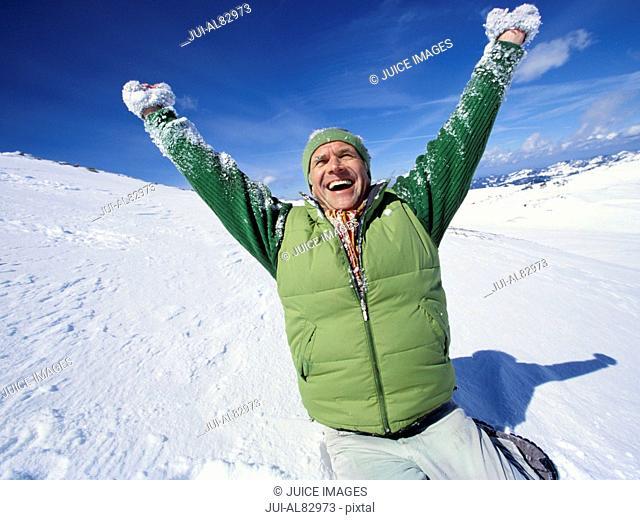 Senior man kneeling in snow with arms raised