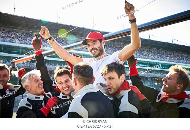 Formula one racing team carrying driver on shoulders, celebrating victory
