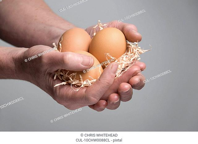 Female hand holding eggs
