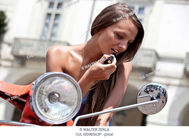 Young woman sitting on scooter, looking in wing mirror, applying lipstick