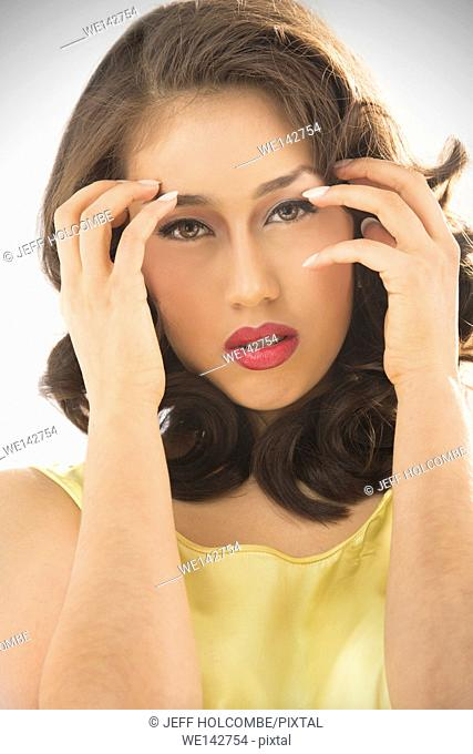 Beautiful young woman head and shoulders portrait in vintage yellow dress, with a direct, glamorous look