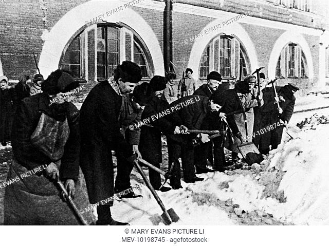 A carefully posed photo showing members of the bourgeoisie forced to clear snow in the streets of Petrograd