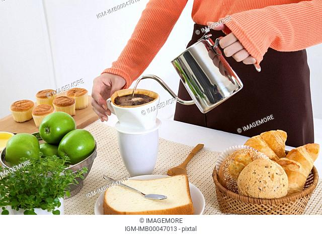 Young woman making coffee in the kitchen for breakfast
