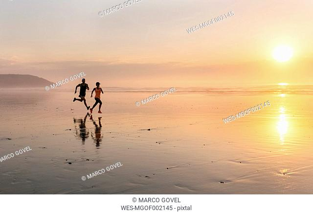 Athletes couple running on the beach at sunset