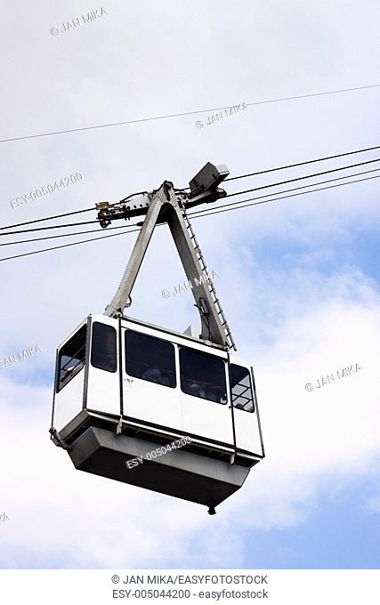 Cable Car on wires over cloudy sky with non-recognisable silhouettes of people inside  Cable Car in Gibraltar