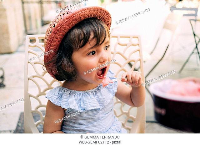 Cute toddler girl eating an ice cream on a terrace