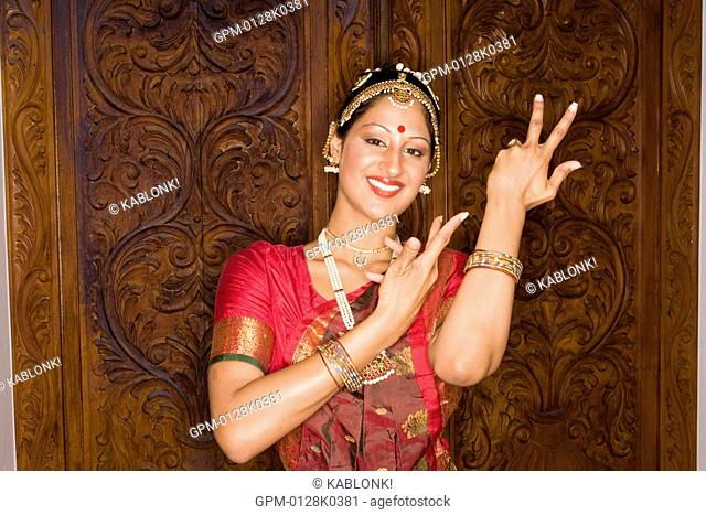 Portrait of Indian woman posing in traditional dress in front of ornate door, looking at camera