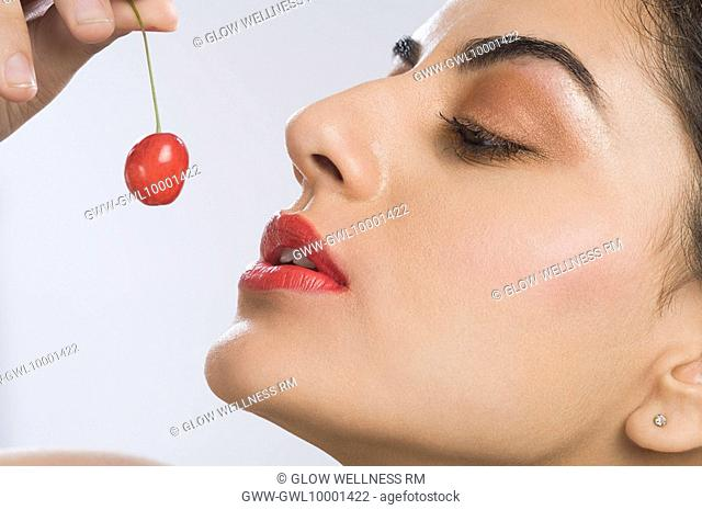 Close-up of a woman eating a cherry