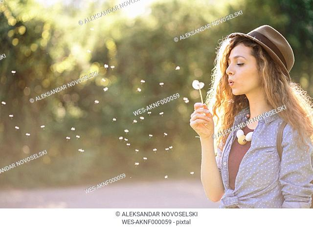Young woman blowing dandelion