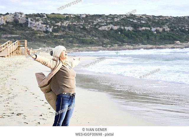Spain, Menorca, happy senior man standing at seashore in winter