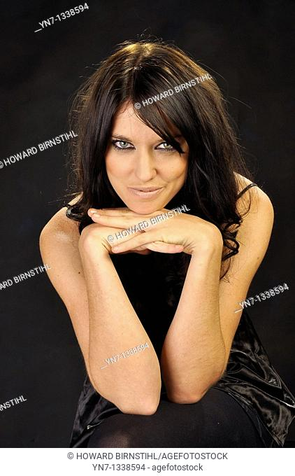 Attractive female model sitting with chin in hands grinning at the camera