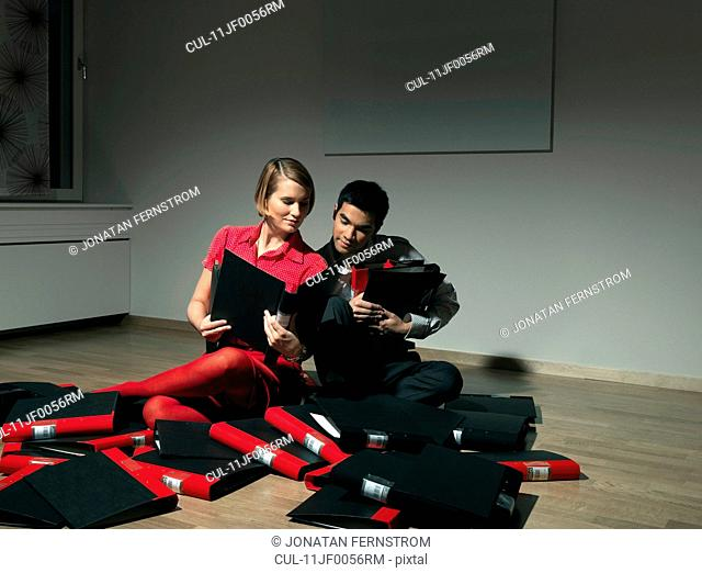 Man and woman playing with binders