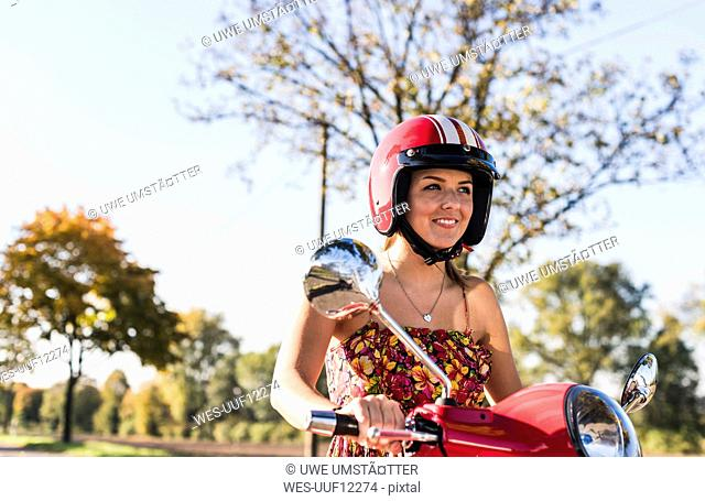 Portrait of smiling young woman on motor scooter
