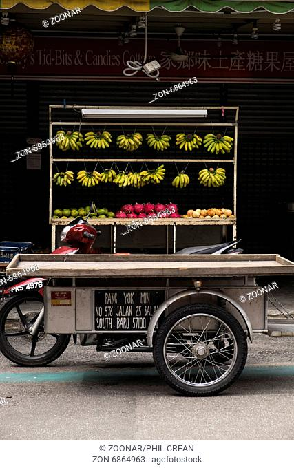 Fruit stall and motorcycle in the Jalan Alor hawkers food street in Kuala Lumpur, Malaysia