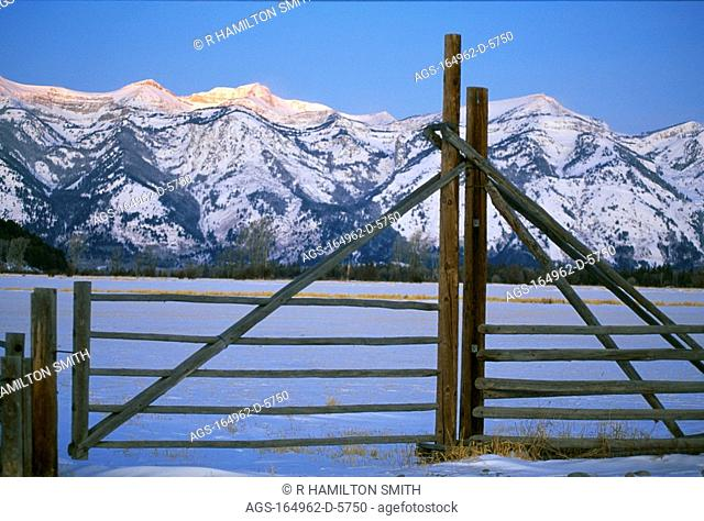 Agriculture - Ranch fence and gate with snow covered mountains in the background / WY