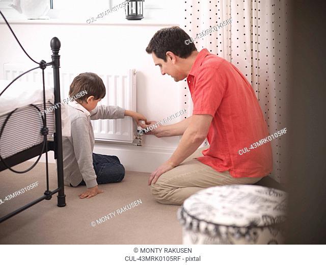 Father and son adjusting radiator