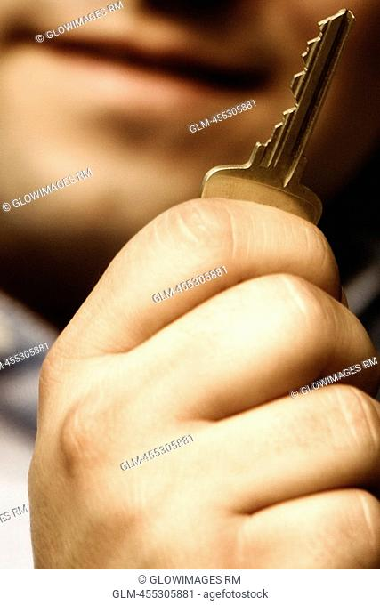 Close-up of a man holding a key