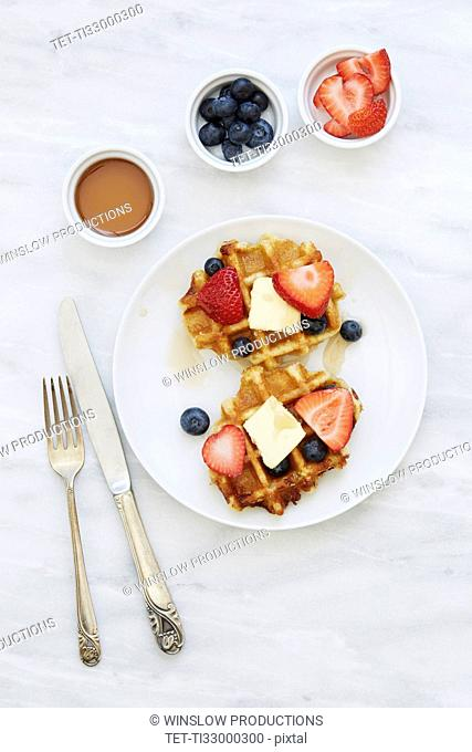 Overhead view of waffles with strawberries and blueberries