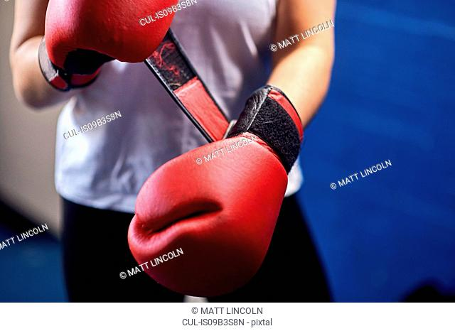 Mid section of female boxer fastening red boxing gloves
