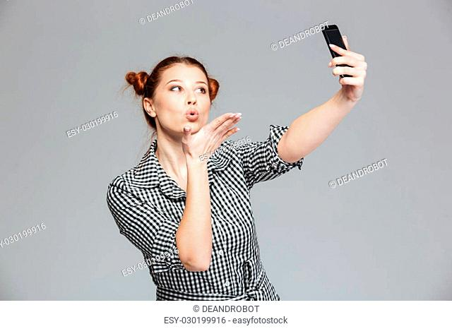 Playful pretty young woman sending kiss and making selfie with mobile phone over grey background