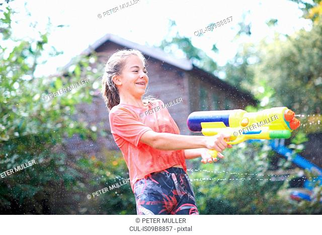 Teenage girl squirting water gun in garden