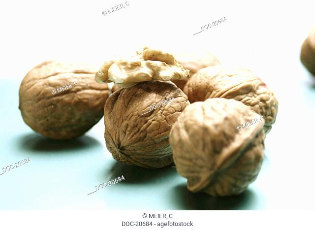 several whole walnuts with a piece of inner nut on white ground