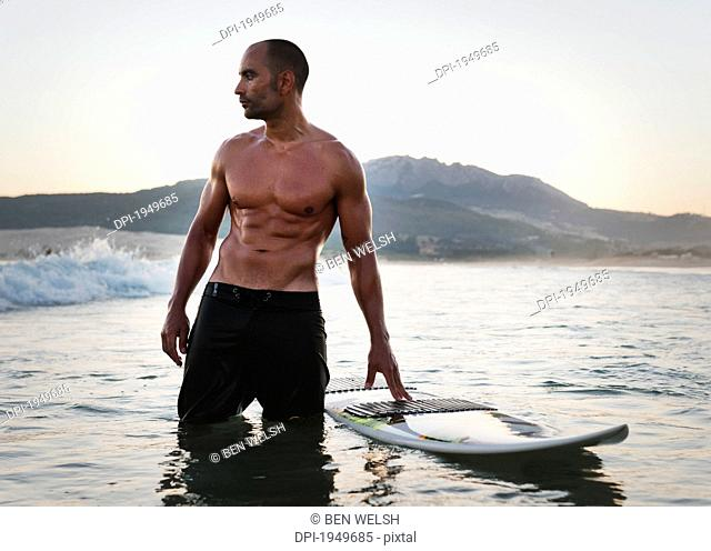 A Man Standing In The Water With His Surfboard Off Valdevaqueros Beach, Tarifa Cadiz Andalusia Spain