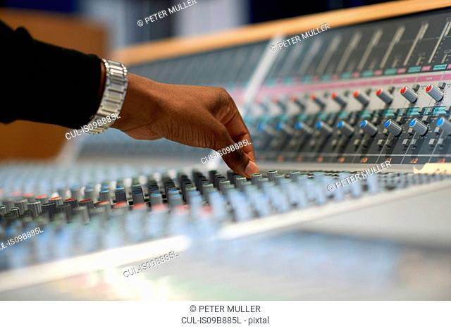 Hand of male college student at sound mixer in recording studio