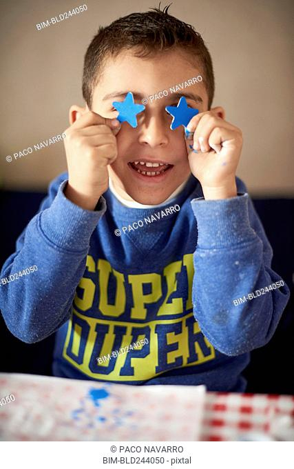 Hispanic boy covering eyes with blue stars at table