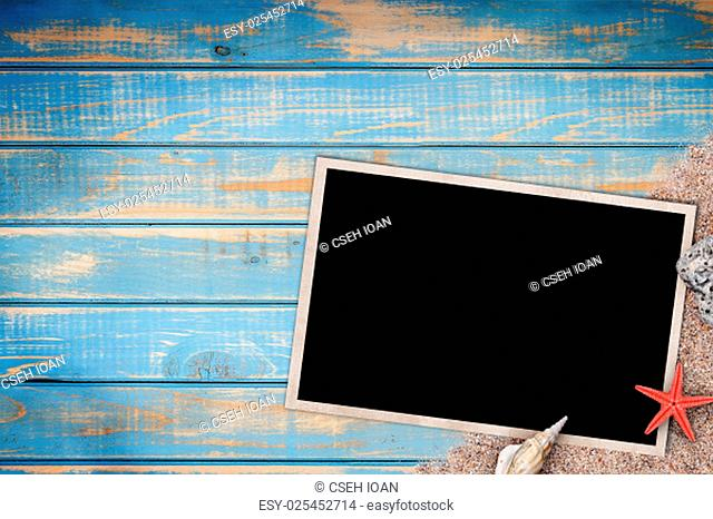 Summer like old style empty photo card lying on blue wooden board