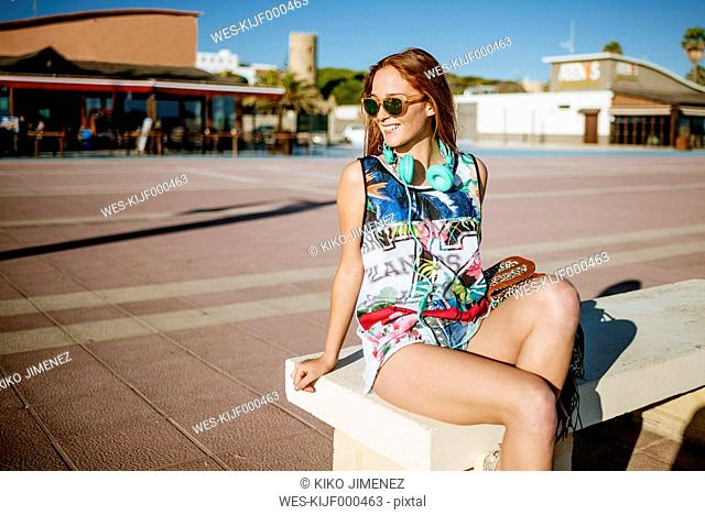 Spain, Chiclana de la Frontera, happy tourist sitting on a bench at sunlight