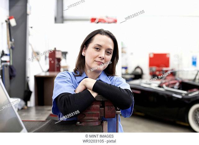 A portrait of a Caucasian female mechanic in a car repair shop