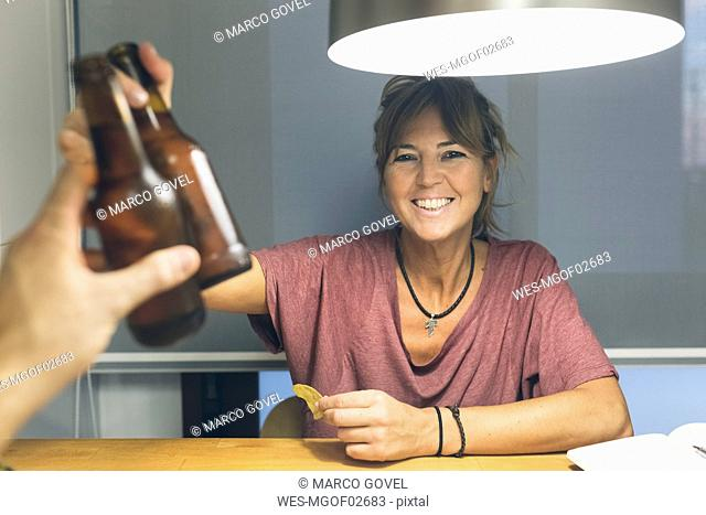 Smiling woman clinking beer bottle