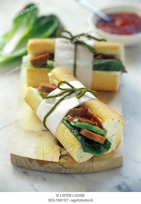 Baguette pieces filled with salad, sausage and ketchup sauce