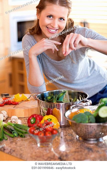 Young woman adding some spices to her meal