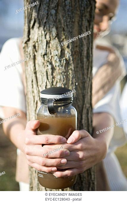 Woman holding a tea kettle around tree trunk