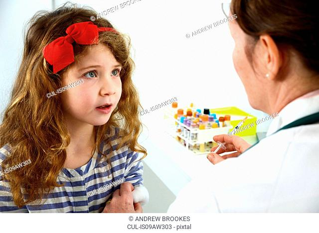 Girl receiving immunisation injection from doctor