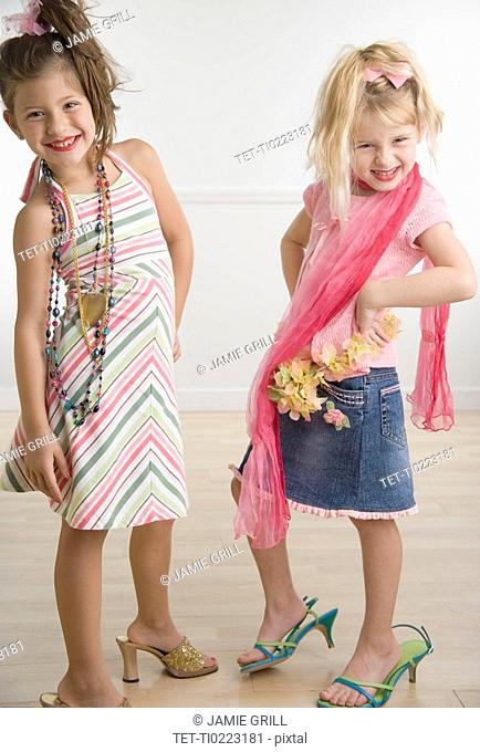 Two young sisters playing dress-up