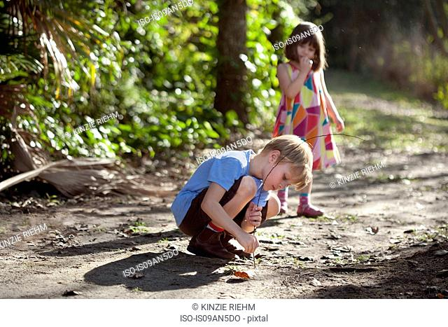 Young boy drawing in dirt with stick, young girl in background