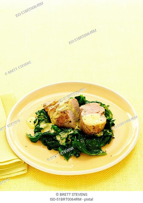 Plate of pork with mustard greens