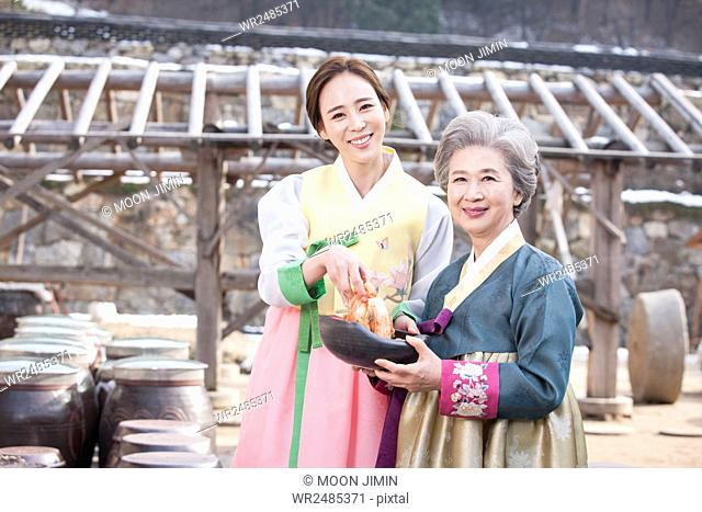 Smiling young woman and old woman in hanbok holding gimchi