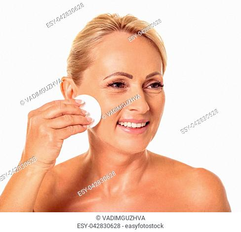 Portrait of beautiful middle aged woman with bare shoulders cleaning her face using cotton disc, looking away and smiling, isolated on white