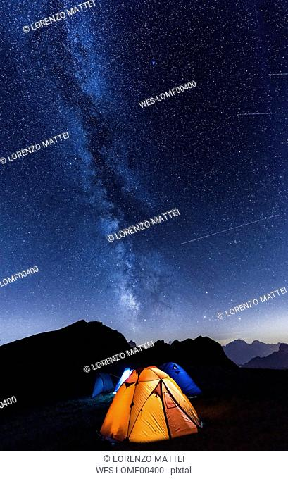 Italy, Dolomites, Milky Way over Monte Pelmo with tents of camp in the foreground
