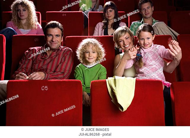 Family sitting in movie theater