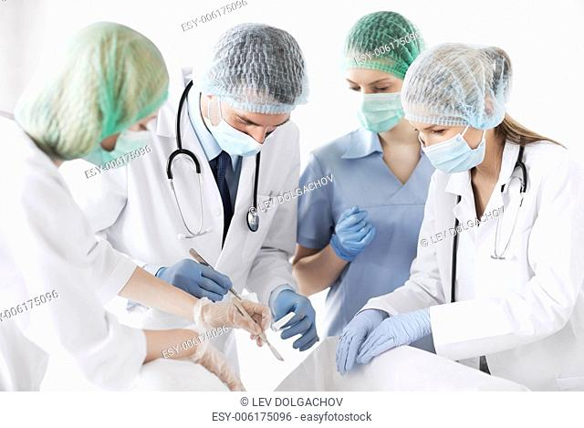 healthcare and medical - young group of doctors doing operation