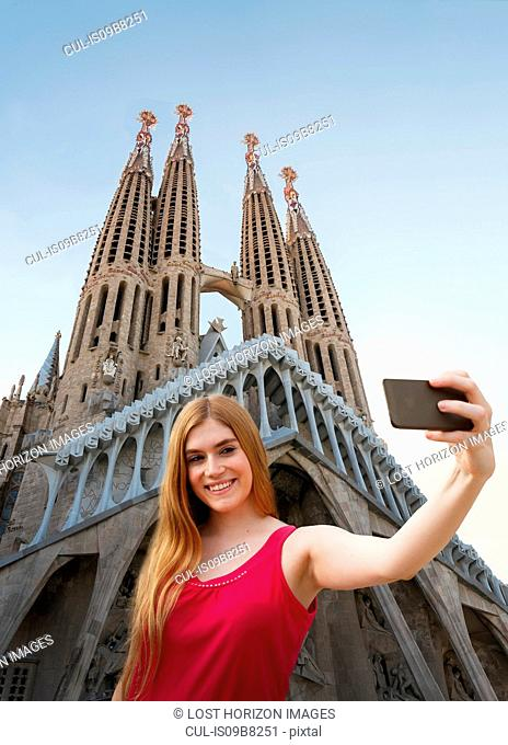 Woman taking selfie infront of Sagrada familia cathedral, Barcelona, Catalonia, Spain, Europe
