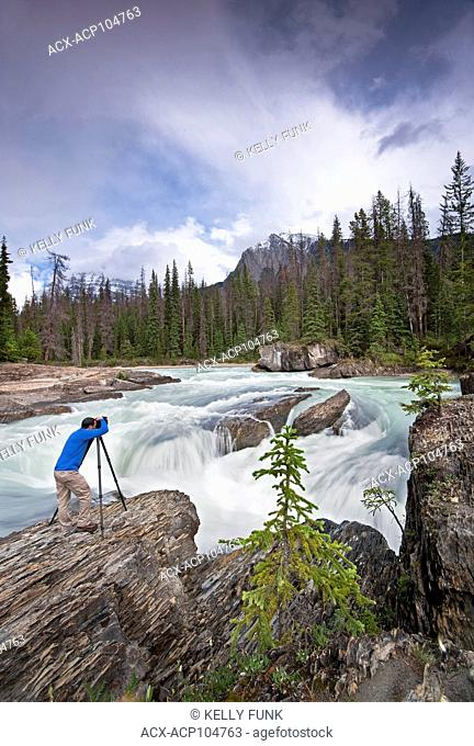 A photographer takes in the beautiful scene at The Natural Bridge and the Kicking Horse River at Yoho National Park, near Field, Rocky Mountain region