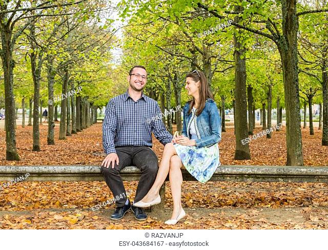 Lovely couple having fun together on a stone bench in a park in autumn