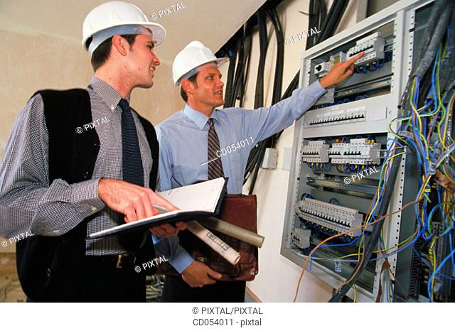 Architects checking electrical installation at construction site